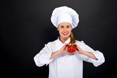 El cocinero de la mujer hace la muestra del corazón de la mano con el tomate sobre fondo oscuro Imagenes de archivo