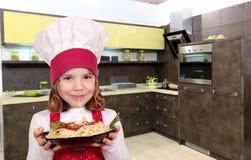 El cocinero de la niña come los espaguetis Imagen de archivo libre de regalías