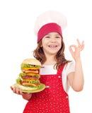El cocinero de la niña con la hamburguesa grande y la mano aceptable firman Imagen de archivo libre de regalías