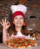 El cocinero de la niña con la pizza y la mano aceptable firman Imagen de archivo libre de regalías