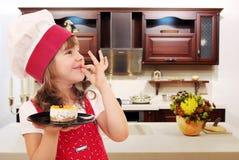 El cocinero de la niña con la torta y la mano aceptable firman adentro la cocina Imagen de archivo libre de regalías