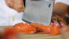 El cocinero de la señora da cortar pescados rojos en la tabla, aperitivo delicioso, cocina asiática almacen de video
