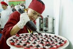 El cocinero de sexo femenino adorna el plato del postre imagenes de archivo