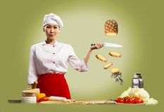 El cocinero de sexo femenino asiático corta la piña Imagen de archivo