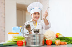 El cocinero de sexo femenino en toca trabaja con la cucharón Imagenes de archivo