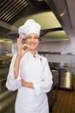 El cocinero de sexo femenino que gesticula muy bien firma adentro la cocina Fotos de archivo libres de regalías