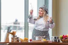El cocinero de sexo femenino que prepara la sopa en cocina brillantemente encendida foto de archivo