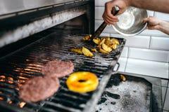 El cocinero de sexo masculino prepara la patata asada a la parrilla Fotos de archivo libres de regalías