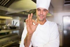 El cocinero de sexo masculino que gesticula muy bien firma adentro la cocina Imagenes de archivo