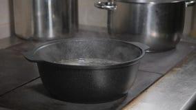 El cocinero del cocinero añade los ingredientes Caldo de carne de vaca tradicional con la verdura, los huesos y los ingredientes  almacen de video