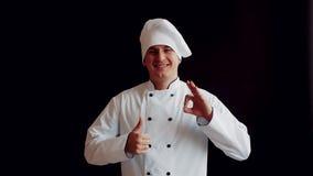 El cocinero del aspecto caucásico en un uniforme blanco con una sonrisa amplia en su cara con demostraciones de una mano manosea  almacen de video
