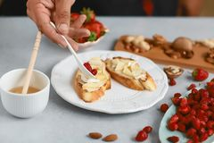 El cocinero del cocinero prepara los bocadillos dulces con las fresas, el queso, el camembert, el brie, las nueces y la miel en e fotografía de archivo libre de regalías