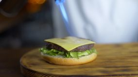 El cocinero derrite el queso con la ayuda del mechero de gas en la chuleta en vías de la fabricación de la hamburguesa en el rest metrajes