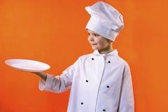 El cocinero divertido del muchacho mantiene una placa blanca limpia su mano imagenes de archivo