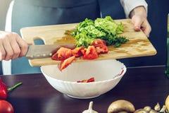 El cocinero en delantal negro corta verduras Concepto de productos respetuosos del medio ambiente para cocinar Imagenes de archivo
