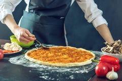El cocinero en delantal negro hace la pizza con sus manos que ponen los ingredientes para la pizza en la tabla Foto de archivo