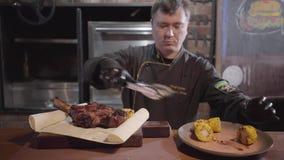 El cocinero en guantes de goma negros del cocinero sirve un plato que separa en el pan fino una rebanada de carne sabrosa asada a metrajes