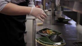 El cocinero en la cocina adorna el plato con verdes en una placa metrajes