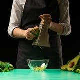 El cocinero en un fondo negro frota el aguacate para cocinar el smoothie verde del detox Comida sana, limpia, concepto de la pérd foto de archivo