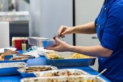 El cocinero en un uniforme azul pone una ensalada en un primer de la bandeja foto de archivo