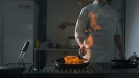 El cocinero enciende para arriba el flambe en una cacerola caliente en la cocina en la cámara lenta, fuego abierto grande en la  almacen de video