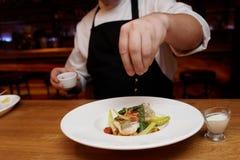 El cocinero está añadiendo la cebolla frita a un plato de pescados Fotografía de archivo