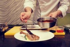 El cocinero está añadiendo la salsa de la baya al plato de las aves de corral, tono azul foto de archivo libre de regalías