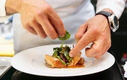 El cocinero está adornando el plato delicioso Imagen de archivo