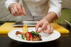 El cocinero está adornando un plato Imagen de archivo libre de regalías