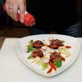 El cocinero está adornando un plato con sésamo Fotografía de archivo