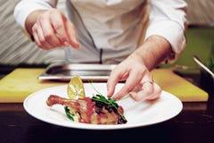 El cocinero está adornando un plato, entonado Imagen de archivo