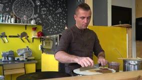 El cocinero está cocinando las crepes grandes finas en el café El cocinero mancha una crema del chocolate en una crepe Alimentos  almacen de metraje de vídeo