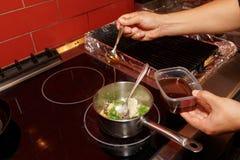 El cocinero está cocinando verduras en estufa Fotografía de archivo libre de regalías