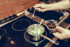 El cocinero está cocinando verduras en la estufa, entonada Imagen de archivo