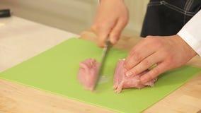 El cocinero está cortando los prendederos de Turquía en una tabla de cortar metrajes