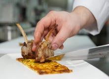 El cocinero está haciendo el plato de la carne Foto de archivo