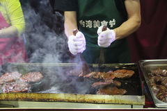 El cocinero está haciendo un filete curruscante en la placa del hierro Foto de archivo