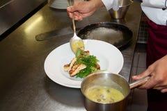 El cocinero está haciendo un plato de pescados Imagen de archivo