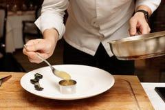 El cocinero está poniendo el puré para platear Imagen de archivo libre de regalías