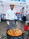El cocinero está preparando un plato nacional de los mariscos Foto de archivo libre de regalías