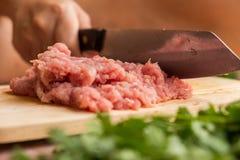 El cocinero está tajando el cerdo crudo en la tabla de cortar de madera con a Fotografía de archivo libre de regalías
