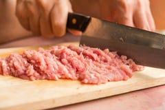 El cocinero está tajando el cerdo crudo en la tabla de cortar de madera con a Imágenes de archivo libres de regalías