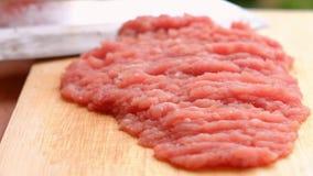 El cocinero está tajando el cerdo crudo en la tabla de cortar de madera con un cuchillo afilado para cocinar en la cocina metrajes