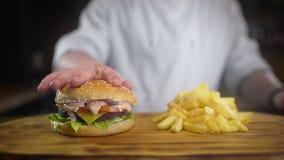 El cocinero exprime goteos deliciosos jugosos de la hamburguesa y de la salsa de él en la cámara lenta, cocinando las hamburguesa almacen de video