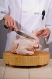 El cocinero fabrica la pierna de pollo Imagen de archivo libre de regalías
