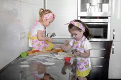 El cocinero feliz del niño de dos niñas con la harina y la pasta en la tabla en la cocina es precioso y hermoso foto de archivo