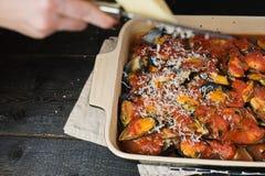 El cocinero frota el queso en los mejillones en salsa de tomate fotos de archivo libres de regalías