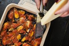 El cocinero frota el queso en los mejillones en salsa de tomate fotografía de archivo libre de regalías