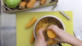 El cocinero frota zanahorias en un rallador en la cocina Visión superior metrajes