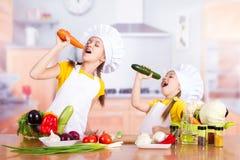 El cocinero gemelo de la muchacha que sostiene verduras como micrófono y canta Fotografía de archivo